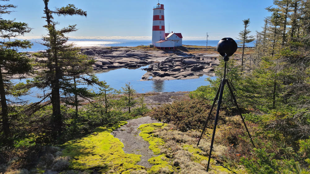 Insta360 Titan surrounded by trees with a view of a lighthouse. Shooting for the immersive virtual reality experience.