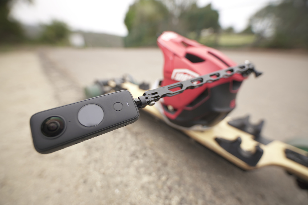 A longboard on the ground with a helmet, which has the Unicorn Mount attached to it, with the Insta360 ONE X2 camera mounted on the end.